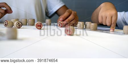 Children Play Russian Lotto On The Table. Playing Kegs With Numbers