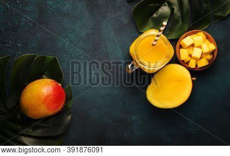 Freshly Squeezed Fresh Mango Juice In Large Glass Jar With Fresh Fruit On Dark Blue Background, Plac