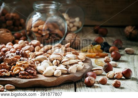 Nuts Set Of Pistachios, Walnuts, Almonds And Hazelnuts On A Wooden Background, Selective Focus