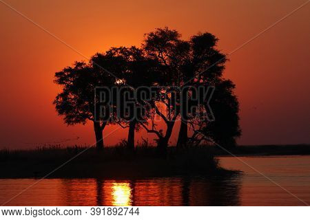 Island In The Chobe River. Sunset Over A Large African River.
