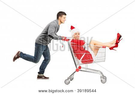 A guy pushing a woman wearing christmas costume in a shopping cart isolated on white background