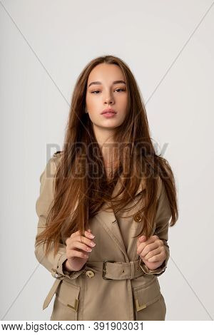 Beautiful Young Girl With Long Hair Posing In Studio In Different Poses Against A Gray Background, F