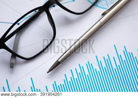 Metal Ballpoint Pen And Glasses For Vision Lie On Documents With Graphs In Office Closeup. End Of Wo