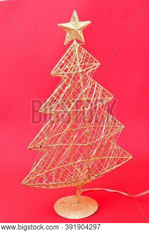 Christmas Toys, Golden Artificial Christmas Tree, Glows From Batteries On A Red Background