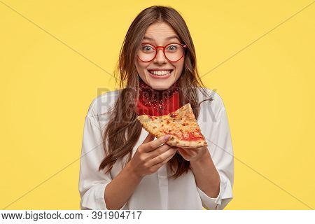 Photo Of Satisfied Woman Holds Piece Of Pizza, Feels Pleased As Spends Free Time With Friends In Piz