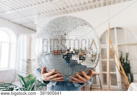 Young Woman Holding Big Disco Ball In Hands. High Quality Photo