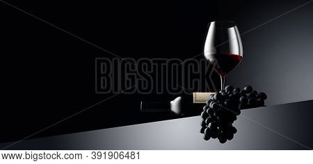 Red Wine And Blue Grapes On A Dark Background. On A Bottle Old Empty Label. Selective Focus. Copy Sp
