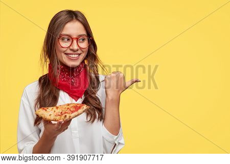 Isolated Shot Of Attractive Smiling Girl Shows Direction To Pizzeria, Eats Tasty Pizza With Cheese A
