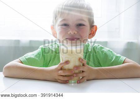 Kid Boy Holding Glass Of Smoothie With Orange, Banana, Curd. Fresh Organic Vegetarian Drink. Baby Fo