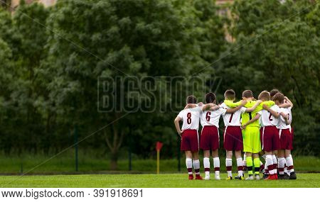 Soccer Boys Standing In A Circle And Huddling Before The Competition Game. Hapyy Kids Making Sports.