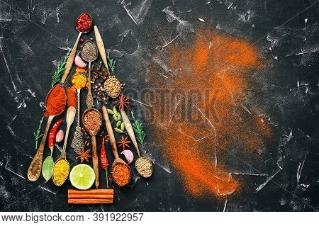 Abstract Christmas Tree Made Of Spices And Seasoning In Spoons. Black Stone Background. Top View, Fl