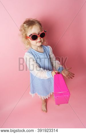 Little Girl Child In Sunglasses With A Pink Redicle.