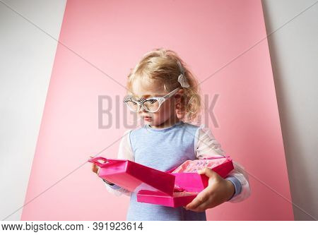 Little Girl Child Plays With A Set Of Childrens Cosmetics.
