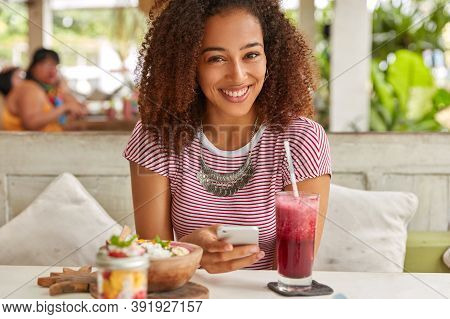 Glad Dark Skinned Woman With Crisp Hair, Reads News On Web Site, Connected To Wireless Internet At C