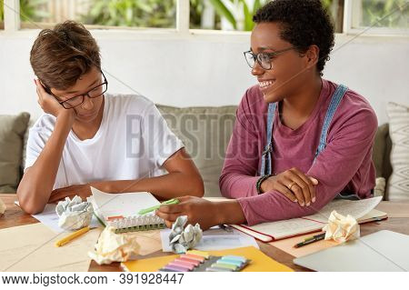 Image Of Mixed Race Boy And Girl Collaborate For Preparing Course Paper, Make Records In Notepad, Si