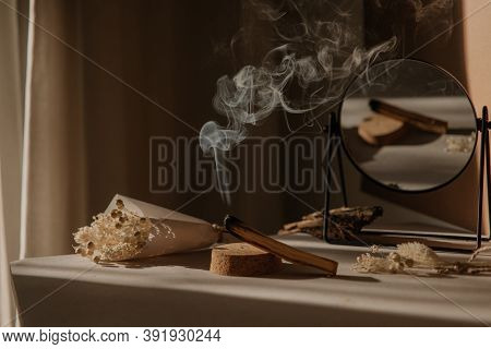 Palo Santo With Jet Of Smoke, Mirror And Dried Flowers On A Neutral Background. Abstract Picture. Mi
