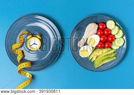 Food And Alarm Clock On Blue Background, Intermittent Fasting Concept.