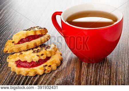 Shortbread Cookies With Raspberry Jam And Linseeds, Red Cup With Tea, On Dark Wooden Table