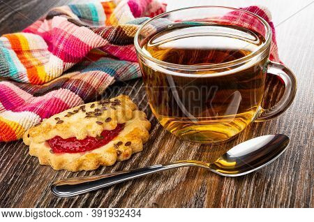 Checkered Napkin, Shortbread Cookie With Raspberry Jam And Linseeds, Transparent Cup With Tea, Teasp