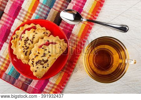 Shortbread Cookies With Raspberry Jam And Linseeds In Red Saucer, Teaspoon On Checkered Napkin, Tran