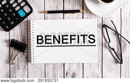 The Word Benefits Is Written In A White Notepad Near A Calculator, Coffee, Glasses And A Pen. Busine