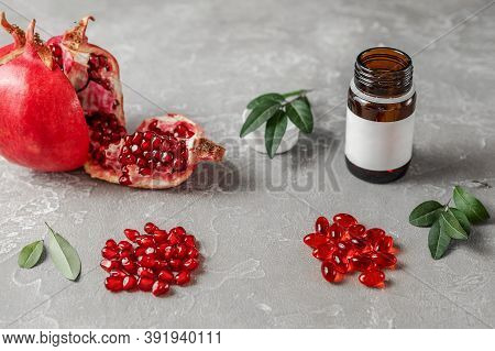 Red Pomegranate Berries With Leaves And Vitamins In Capsules On A Rough Gray Background Concept Of H