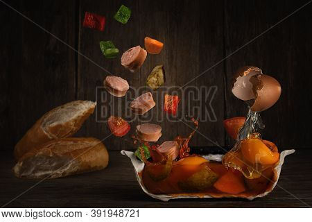 Cutaway vegetable soup with eggs, sausages in levitation and baguette on dark background