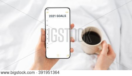 2021 New Year Goals Checklist. Hands Holding Smartphone With Future Goal And Plans List For Upcoming