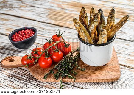 Fried Smelt In The Pan On The Table With Tomatoes And Pepper. White Background. Top View