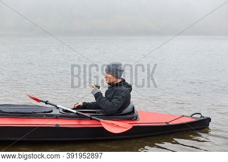 Man Paddles Red And Black Kayak And Sitting With Paddle, Holds Mug With Hot Coffee Or Tea On River O