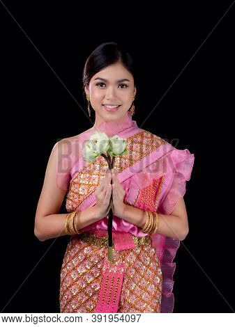 A Charming Thai Woman In Ancient Thai Dress Holding A Lotus Flower That Is Used For Worshiping Relig