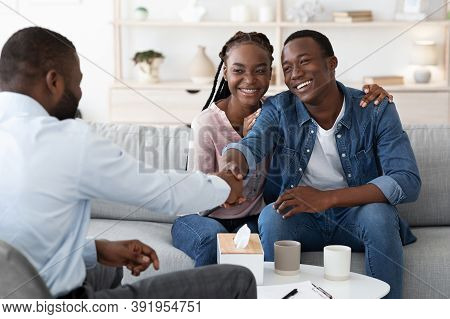 Happy Black Spouses Thankful To Family Counselor After Successful Marital Therapy Session, Shaking H