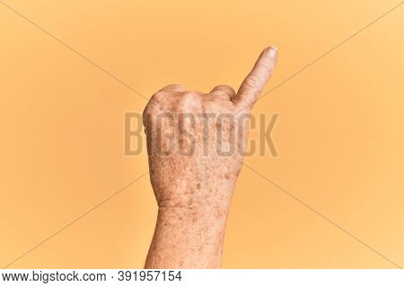 Senior caucasian hand over yellow isolated background showing little finger as pinky promise commitment, number one