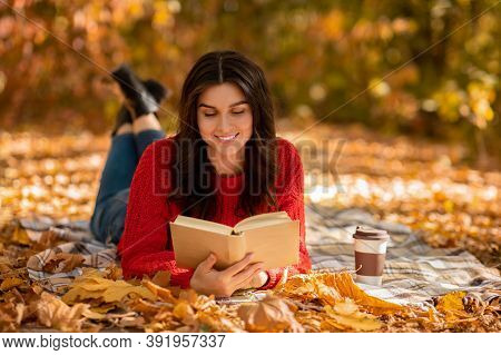 Smiling Young Woman In Woolen Sweater Lying On Picnic Blanket With Book And Coffee At Autumn Park, B