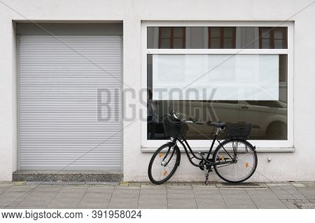 Blank Vacancy Sign Or Poster With Copy Space In Empty Store Window With Bicycle Parked Outside Close