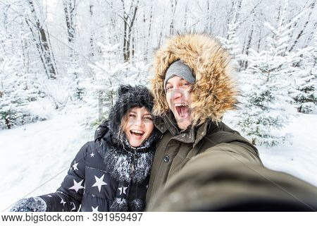 Technologies And Relationship Concept - Happy Smiling Couple Taking A Selfie In A Winter Forest Outs