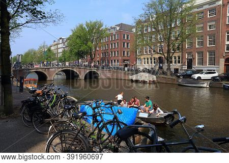 Amsterdam, Netherlands - July 7, 2017: People Ride A Rental Boat On Keizersgracht Canal In Amsterdam