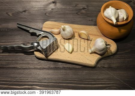 On A Dark Wooden Background Is A Cutting Board With Garlic And A Tool For Chopping Garlic Cloves. Ne