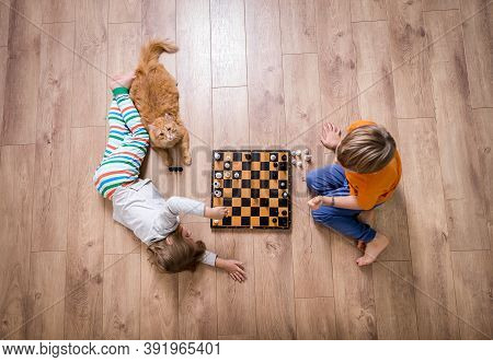 Top View Of Concentrated Child Boy Developing Strategy, Playing Board Game With Sister. Preschool Ki