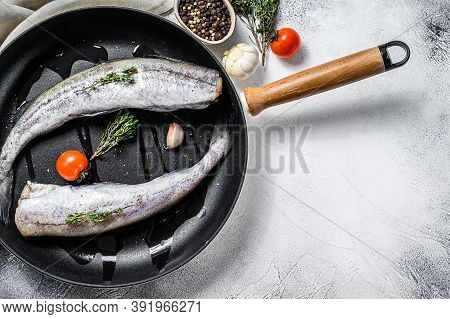 Raw Pollock Fish In A Pan. Organic Seafood. Gray Background. Top View. Copy Space