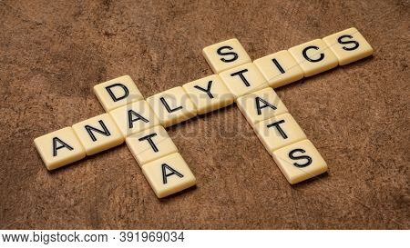 analytics, data and stats crossword in ivory letter tiles against textured handmade paper, discovery, interpretation, and communication of meaningful patterns in data