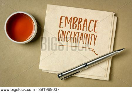 embrace uncertainty motivational note - handwriting on a napkin with a cup of tea, unknown future, change, risk and chance concept