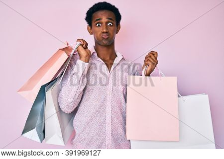 African handsome man holding shopping bags puffing cheeks with funny face. mouth inflated with air, catching air.