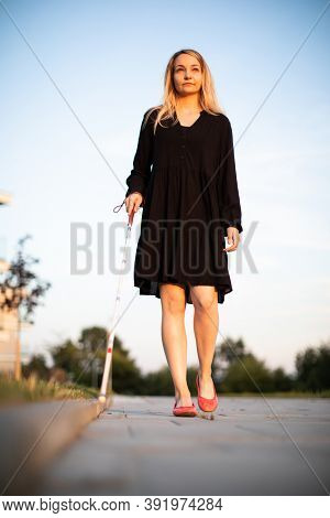 Blind woman walking on city streets, using her white cane to navigate the urban space better and to get to her destination safely
