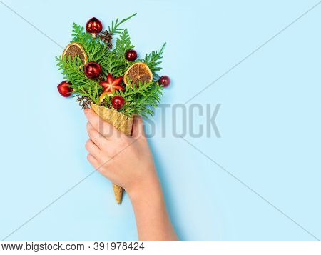 A Female Hand Holds A Favela Horn With Thuja Sprigs And Christmas Toys On A Blue Background. New Yea