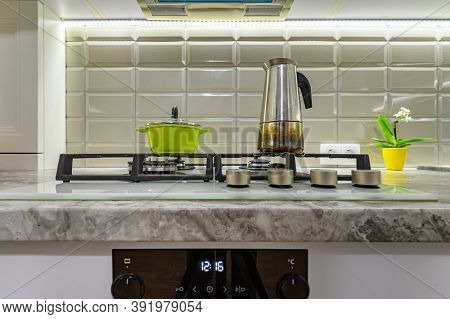Closeup to stove on white cozy and comfy contemporary classic kitchen interior with wooden furniture, front view