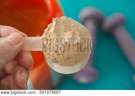Man Holding A Scoop Of Chocolate Soy Protein Isolate Powder In His Hand. Close Up.
