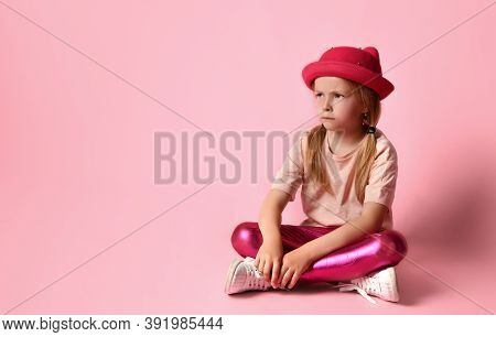 Adorable Little Blonde Girl In Hat, T-shirt, Leggings And White Sneakers. She Looking Frowned, Sitti
