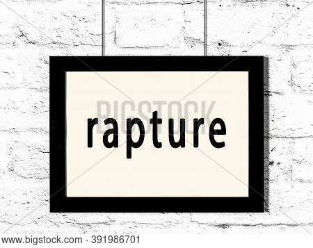 Black Wooden Frame With Inscription Rapture Hanging On White Brick Wall
