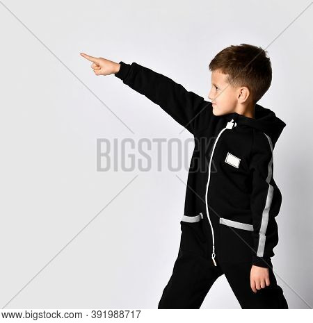 Handsome Boy In Black Warm Jumpsuit Pointing Finger Forward To Copy Space Looking Aside. Side View C